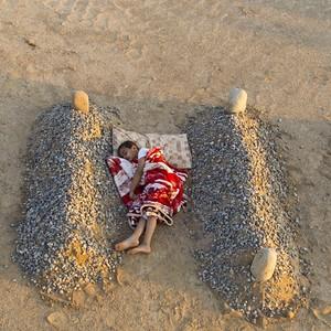 Syryjski chłopciec, śpiący między grobami rodziców? Fotograf zaprzecza